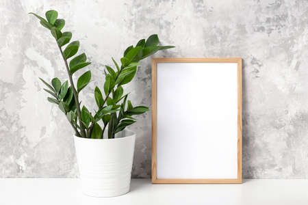 Wooden vertical frame with white blank card, and green houseplant flower in pot on table on gray concrete wall background. Mockup Template for your design, text.