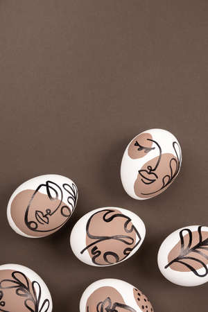 Happy Easter concept. Surreal faces on eggs on brown background. Art und Online style. Top view Flat lay Copy space.