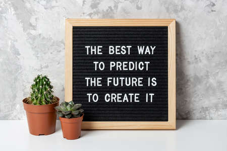 The best way to predict the future is to create it. Motivational quote on letter board, cactus, succulent flower on white table. Concept inspirational quote of the day. Front view. Stock fotó