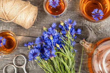 Cups of herbal tea, transparent teapot and blue cornflowers flowers on wood background. Top view Flat lay