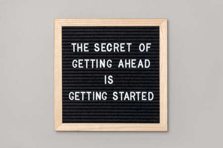 The secret of getting ahead is getting started. Motivational quote on black letter board on gray background. Concept inspirational quote of the day. Greeting card, postcard.