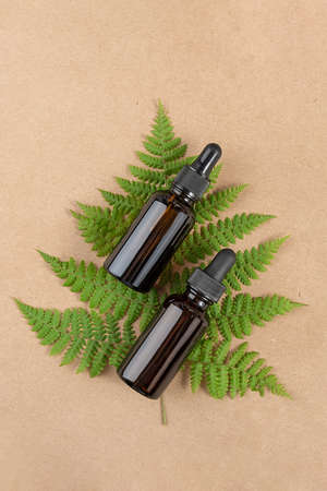 Two brown glass bottles with serum, essential oil or other cosmetic product and green fern leaves on craft beige background. Natural Organic Spa Cosmetic Beauty concept Top view Close-up. Stock fotó