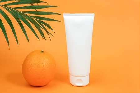 White blank cosmetic bottle, tube of cream, lotion for body, face or hand, orange fruit and branch of palm. Concept cosmetics with vitamin C, antioxidants or anti-cellulite. Mockup Front view.