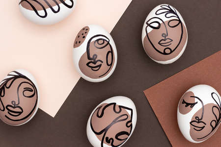 Happy Easter concept. Surreal faces on eggs on brown background. Art und Online style. Top view Flat lay.
