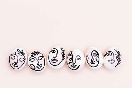Happy Easter concept. Surreal faces on eggs on pink background. Art und Online style. Top view Flat lay Copy space. Stock fotó
