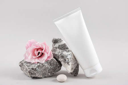 White blank cosmetic bottle tube, stone and pink flower on gray background. Natural Organic Spa Cosmetic Beauty Concept. Front view Mock up.
