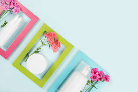 Cosmetics for skin care face, body, hands. White blank cosmetic bottle, tube, jar, flowers in bright frames on blue background. Creative Cosmetic Beauty Concept. Mockup Top view Copy space. Stock fotó