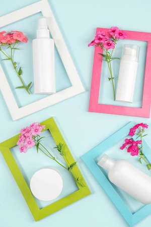 Cosmetics for skin care face, body, hands. White blank cosmetic bottle, tube, jar, flowers in bright frames on blue background. Creative Cosmetic Beauty Concept. Mockup Top view. Stock fotó