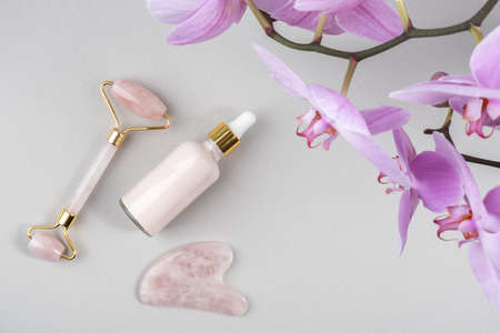 Crystal rose quartz facial roller, massage tool Gua sha and anti-aging collagen, serum in glass bottle on gray background. Facial massage for natural lifting, Beauty concept Top view Copy space.