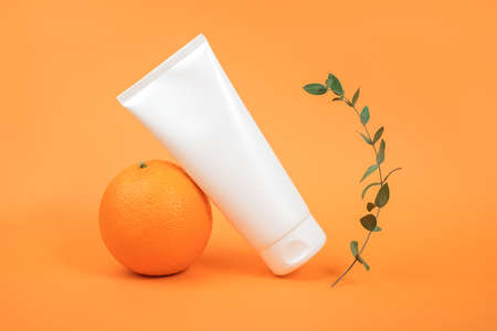 White blank cosmetic bottle, tube of cream, lotion for body, face or hand, orange fruit and green branch eucalypt. Concept cosmetics with vitamin C, antioxidants or anti-cellulite. Mockup Copy space.