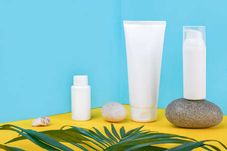 White blank cosmetic tube, bottle with sunscreen, sun cream, moisturizing lotion, rock and green leaf on blue, yellow background. Concept skin care in sea beach holidays in summer vacation.