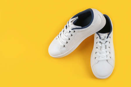 White sports shoes, sneakers with shoelaces on a yellow background. Sport lifestyle concept Top view Flat lay Copy space. Stock fotó