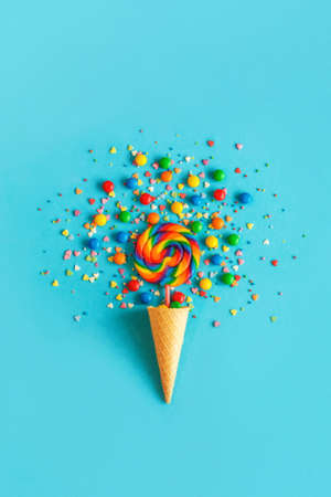 Ice cream waffle cone with colorful lollipop on stick, scattering of multicolored sweets and confectionery topping on blue background. Greeting card, template with bright colorful color palettes.
