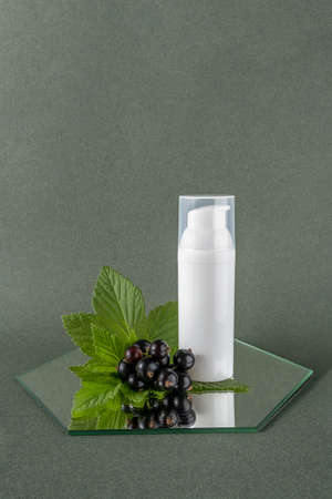 One white bottle with cosmetic product and sprig of black currant on mirror, green background. Natural Organic Beauty Cosmetic concept. Front view.