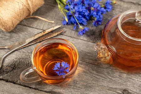 Cup of herbal tea, transparent teapot and blue cornflowers flowers on wood background. Top view Flat lay