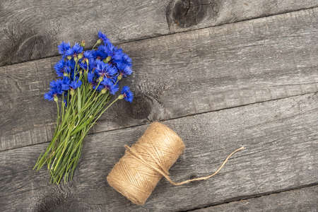 Bouquet of blue cornflowers flowers and a ball twine on a wooden background with copy space. Top view Flat lay.