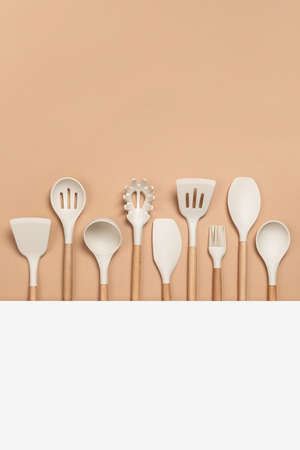 Cooking utensil set. Silicone kitchen tools with wooden handle on beige background with copy space. Top view Flat lay. Banco de Imagens