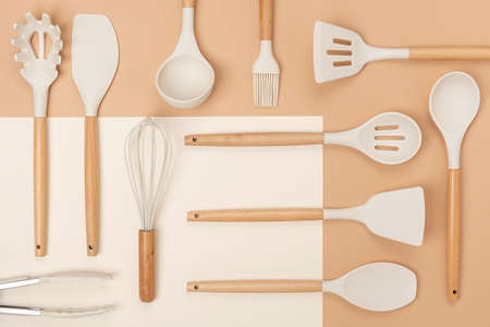 Pattern made from cooking utensil set. Silicone kitchen tools with wooden handle on beige background. Top view Flat lay.
