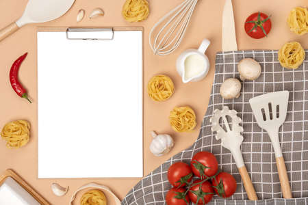 Clipboard with white paper, ingredients for making pasta and cooking utensil, mockup. Template for cooking recipes or your design. Top view Flat lay. Banco de Imagens