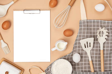 Clipboard with white paper, baking ingredients and cooking utensil, mockup. Template for cooking recipes or your design. Top view Flat lay. Banco de Imagens