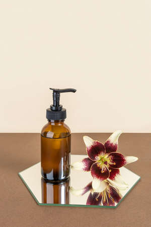 Brown glass bottle with pump of cosmetic products and lily flower on mirror, beige background. Natural Organic Spa Beauty Cosmetic concept Mockup.