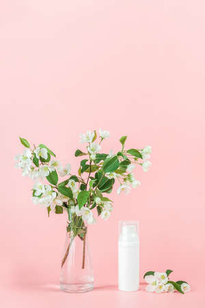 One white blank cosmetic tube bottle and flower, blooming branch on pink background. Natural Organic Spa Cosmetic Beauty Concept. Mockup Front view.