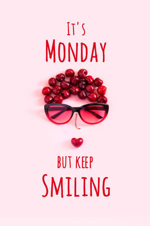 Positive motivational quote. It's Monday but keep smiling text and abstract image young woman from sweet cherry and glasses on pink background. Concept inspirational quote of the day.