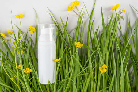 One white bottles with cosmetic product among the green grass, yellow flowers on white background. Natural Organic Spa Cosmetic concept Mockup.
