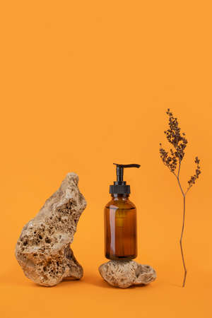 Brown glass bottle with cosmetic product on stone and dried flowers on orange background. Natural Organic Spa Cosmetic concept Front view.