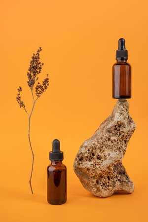Serum or essential oil in brown glass bottles with pipette on stone and dried flowers on orange background. Natural Organic Spa Cosmetic concept Front view.