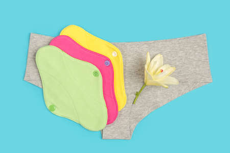 Colored eco reusable menstrual pads and gray panties on blue background. Health care and zero-waste, no plastic concept. Top view Flat lay Close-up.