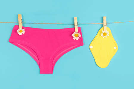Yellow eco reusable menstrual pads and pink panties with chamomile flowers on washing line, blue background. Health care and zero-waste, no plastic, eco-friendly concept.