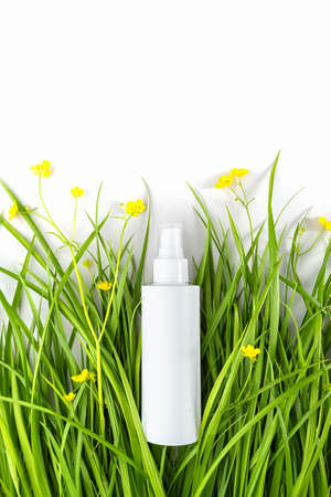 One white spray bottle with cosmetic product among the green grass, yellow flowers on white background. Natural Organic Spa Cosmetic concept Mockup.
