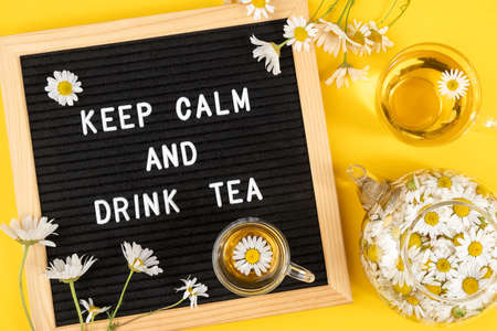 Keep calm and drink tea. Motivational quote on black letter board and herbal chamomile tea on yellow background. Concept inspirational quote of the day. Flat lay Top view.