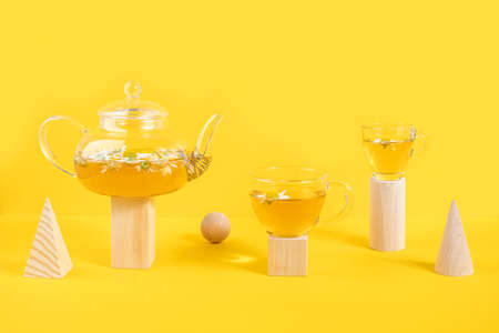 Two cups of camomile tea, transparent teapot on wood geometric shape, yellow background. Creative concept Natural Chamomile Tea. Top view Flat lay.