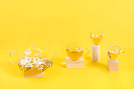 Three cups of camomile tea, transparent teapot on wood geometric shape, yellow background. Creative concept Natural Chamomile Tea. Top view Flat lay.