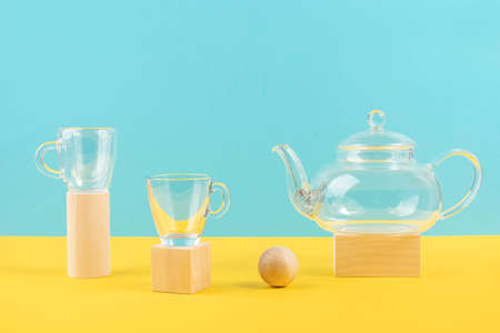 Empty glass transparent tea set. Teapot and and two cups standing on wooden geometric shapes, yellow and blue background. Front view.