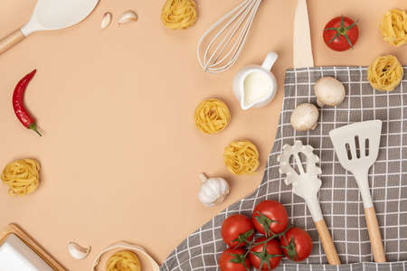 Ingredients for making pasta and cooking utensil with copy space on light brown background. Template for cooking recipes or your design. Top view Flat lay.