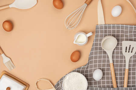 Baking ingredients and cooking utensil with copy space on light brown background. Template for cooking recipes or your design. Top view Flat lay.