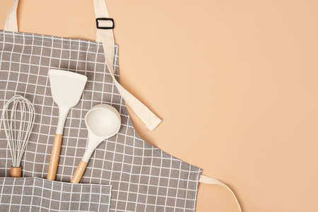 Cooking background. Flat kitchen accessories. Apron and silicone cooking utensil with wooden handle on beige background with copy space. Top view Flat lay. Stock fotó