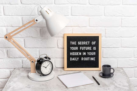 The secret of your future is hidden in your daily routine. Motivational quote on letter board, alarm clock, lamp on workplace. Concept inspirational quote of the day. Front view.