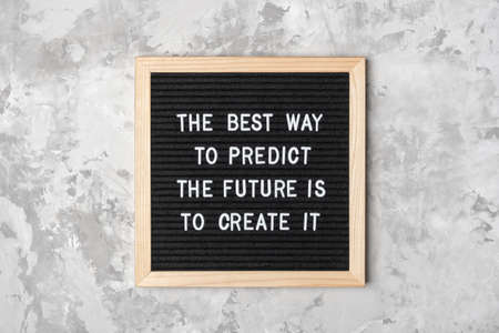 The best way to predict the future is to create it. Motivational quote on black letter board on gray background. Concept inspirational quote of the day. Greeting card, postcard. Stock fotó