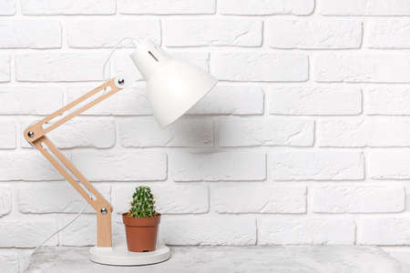 Modern table lamp and cactus on the table, against the background of a white brick wall. Workplace, front view, copy space.