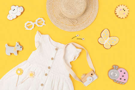 Stylish summer set of child clothes. White dress, the straw hat, sunglasses and accessories on yellow background. Fashion girl lookbook concept. Top view Flat lay.