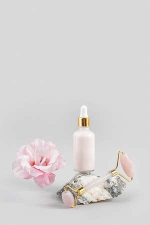 Crystal rose quartz facial roller, cosmetic dropper bottle on stone and beautiful flower on gray background. Facial massage for natural lifting, Beauty concept Front view. Stock fotó
