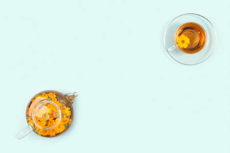 Cups of herbal tea, transparent teapot with calendula flowers on blue background. Calming drink concept. Copy space Flat lay Top view.