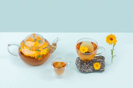 Cups of herbal tea, transparent teapot with calendula flowers and stones on blue background. Calming drink concept. Stock fotó