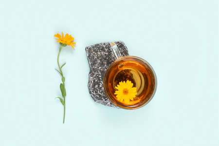Cup of herbal tea on stone and calendula flower on blue background. Calming drink concept. Stock fotó