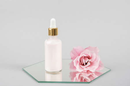 One glass dropper bottle and pink beautiful flower on mirror, gray background. Natural Organic Spa Cosmetic concept. Front view.