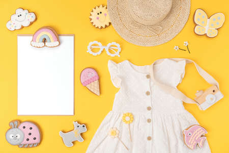 Stylish summer set of child clothes. White blank card, cotton dress, straw hat, sunglasses and funny cookies gingerbread on yellow background. Fashion girl lookbook concept. Top view Flat lay Mockup.